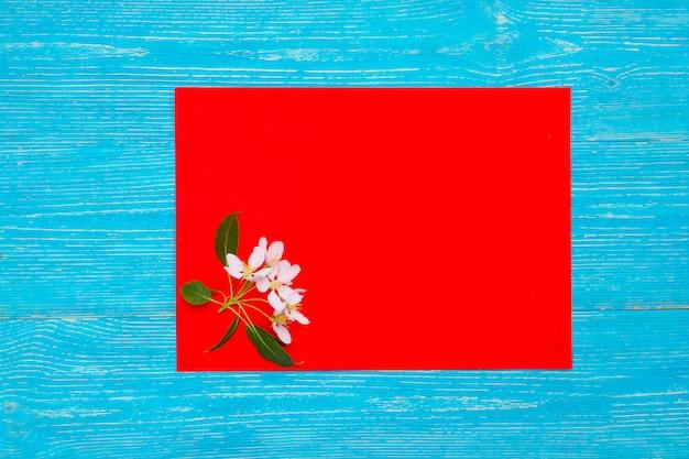 Fleurs de pomme sur une carte en papier rouge sur des planches en bois turquoise
