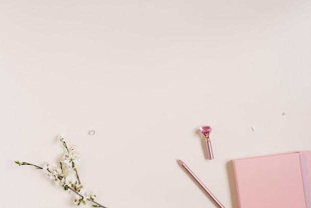 Fleurs de pommier blanches, un bloc-notes rose et un stylo rose sur fond beige
