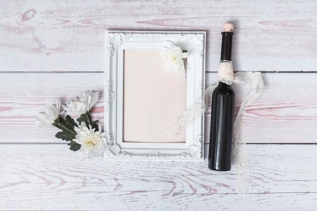 Fleurs près du cadre photo avec du papier et une bouteille