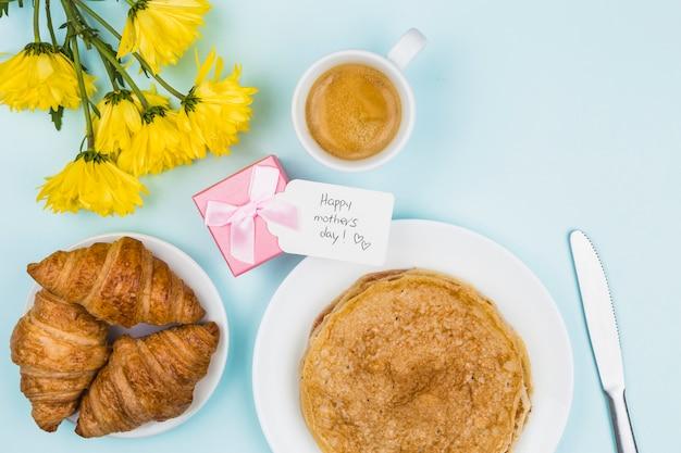 Fleurs près du présent avec étiquette et assiettes avec des crêpes et des croissants
