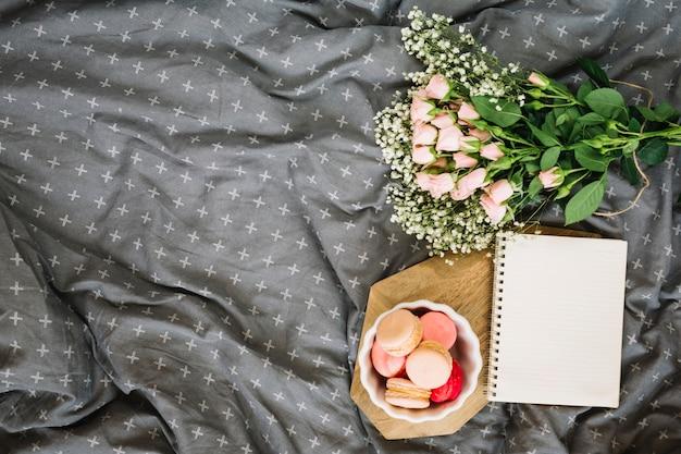 Fleurs près de macarons sucrés et bloc-notes