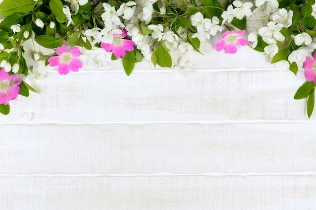 Fleurs de printemps blanches et roses sur fond floral de table en bois blanc