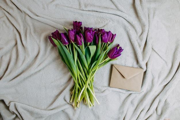 Fleurs de printemps, bouquet de tulipes violettes et enveloppe sur plaid beige.