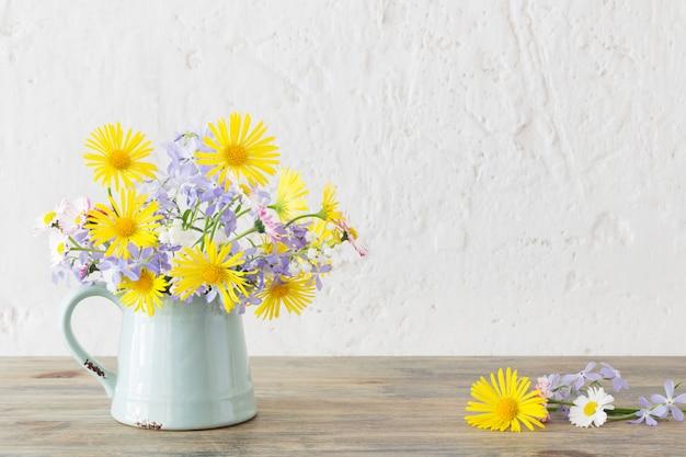 Fleurs de printemps en cruche vintage sur table en bois