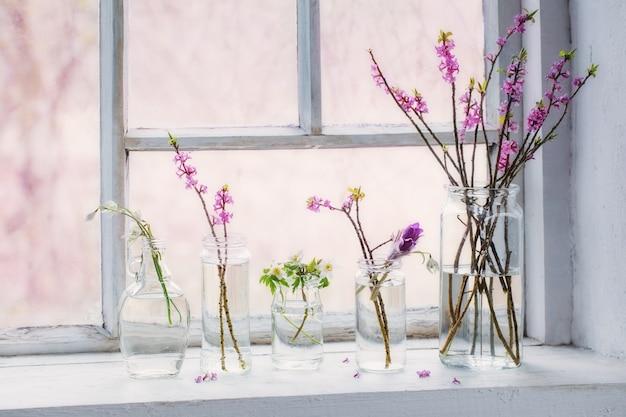 Fleurs de printemps dans des bocaux sur le vieux rebord de la fenêtre blanche