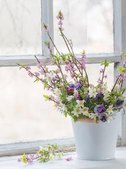 Fleurs de printemps dans un seau blanc sur le vieux rebord de la fenêtre blanche