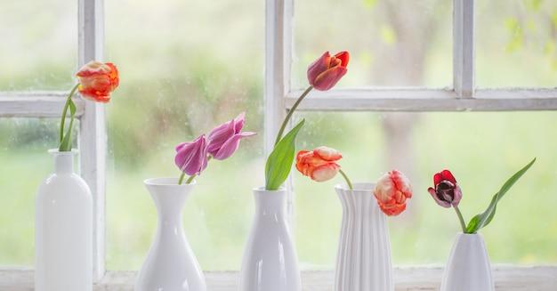 Fleurs de printemps dans un vase blanc sur le vieux rebord de la fenêtre