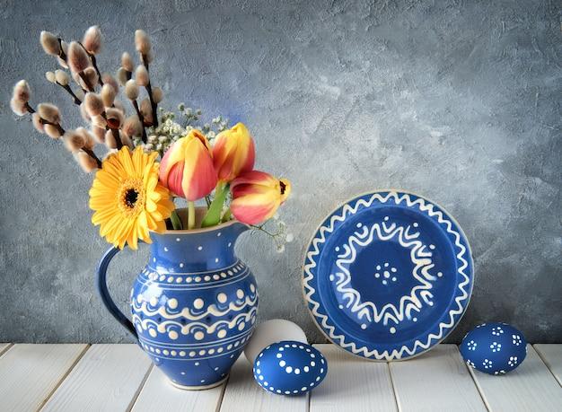 Fleurs de printemps en pichet en céramique bleue avec assiette assortie et oeufs de pâques