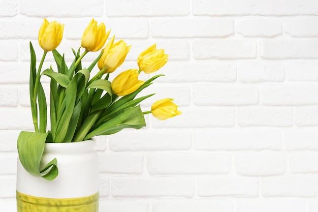 Fleurs de printemps de tulipe dans un vase sur mur de briques décoratives
