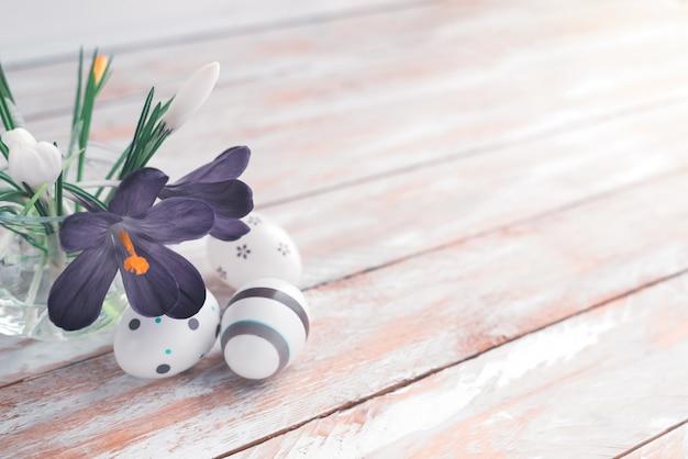 Fleurs de printemps violet en vase et oeufs de pâques sur un fond en bois blanc avec espace de copie.