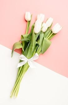 Fleurs de printemps. vue de dessus des tulipes blanches sur fond rose et blanc double couleur