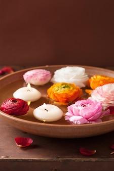 Fleurs de renoncule et bougies dans un bol pour spa