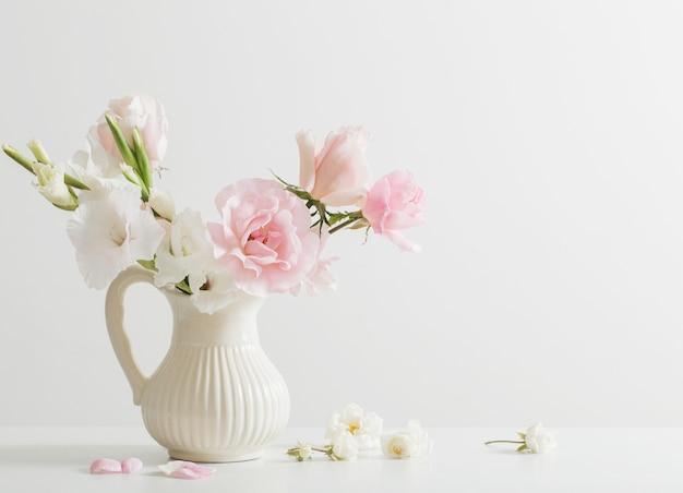 Fleurs roses et blanches dans un vase sur fond blanc