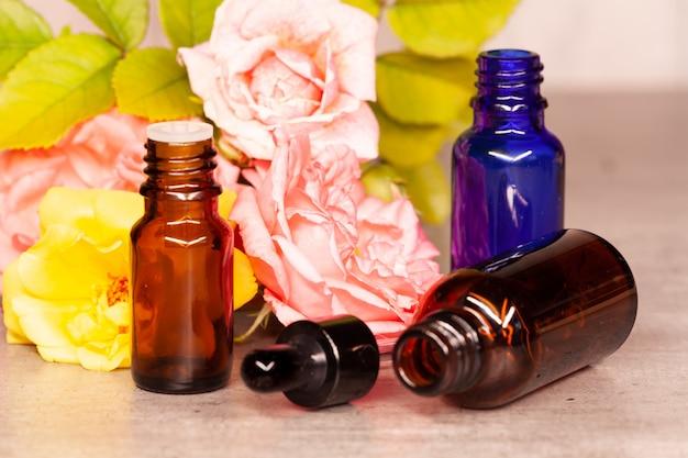 Fleurs de roses et bouteilles d'huiles essentielles pour l'aromathérapie