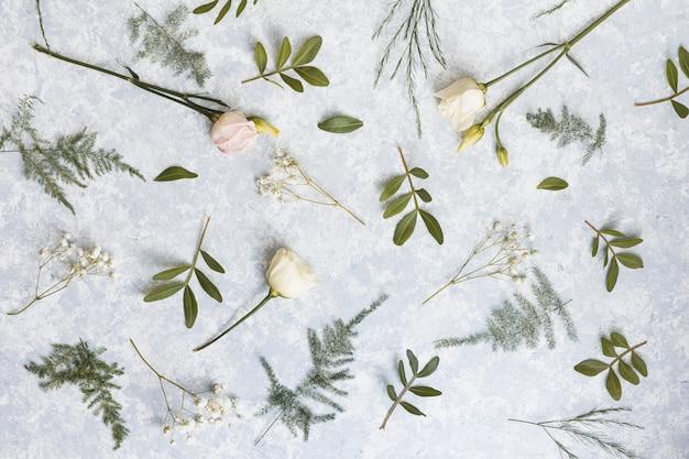 Fleurs roses avec des branches de plantes vertes sur la table