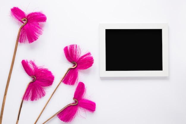 Fleurs roses avec cadre vide sur la table