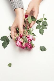 Fleurs roses dans les mains de la femme, vue de dessus, petites roses roses