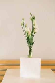Fleurs roses dans un vase avec du papier vierge