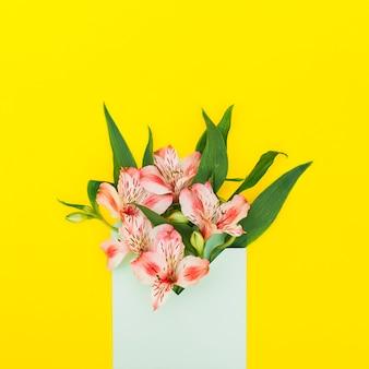 Fleurs roses en enveloppe sur une table jaune