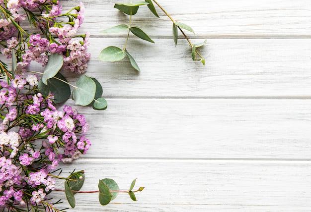 Fleurs roses et eucalyptus sur fond en bois