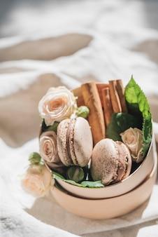 Fleurs roses avec des macarons et de la cannelle sur le récipient sur le drap blanc