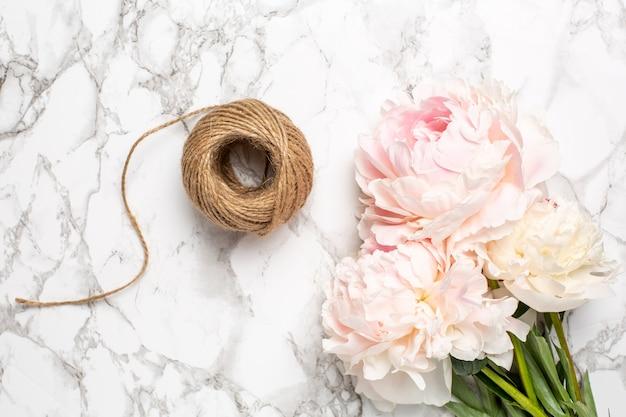 Fleurs roses pivoine et ficelle sur une surface en marbre. article de vacances et d'été.