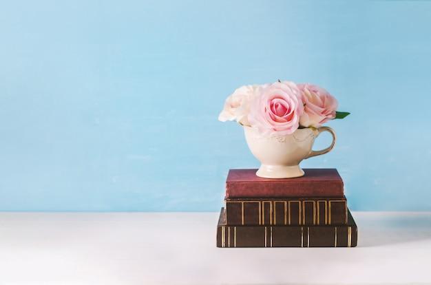 Fleurs roses roses artificielles dans une tasse blanche avec un vieux livre