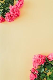 Fleurs roses roses avec bordure de cadre espace copie vierge sur jaune