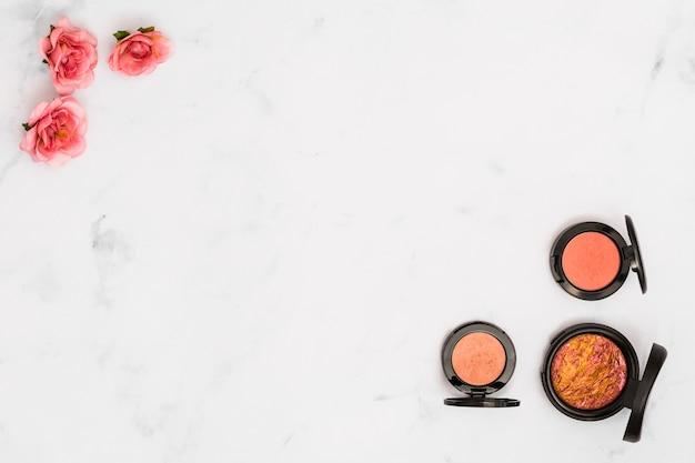 Fleurs roses roses et poudre compacte au coin du fond blanc