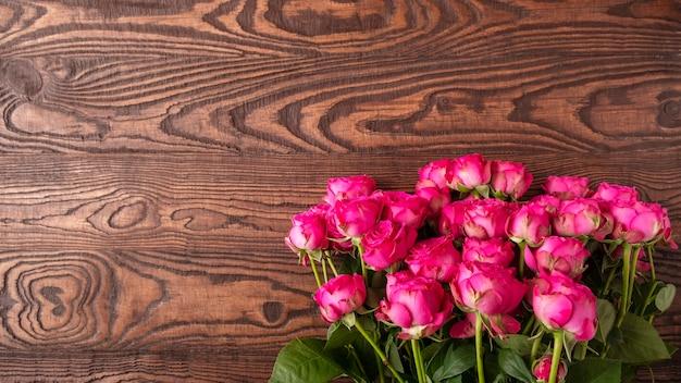 Fleurs roses roses sur une surface en bois