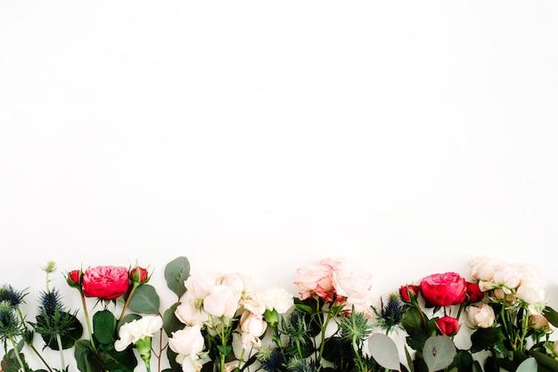 Fleurs roses rouges et beiges, fleur d'eringium, branches et feuilles d'eucalyptus. mise à plat, vue de dessus