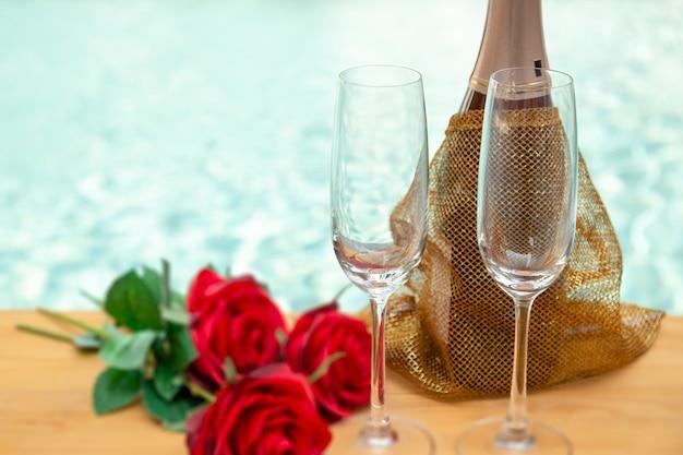 Fleurs roses rouges et bouteille de champagne