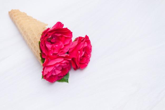 Fleurs roses rouges dans un cône de gaufre sur fond en bois blanc. mise à plat, vue de dessus, fond floral.