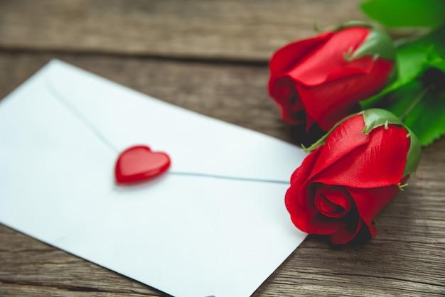 Fleurs roses rouges et lettre sur une table en bois