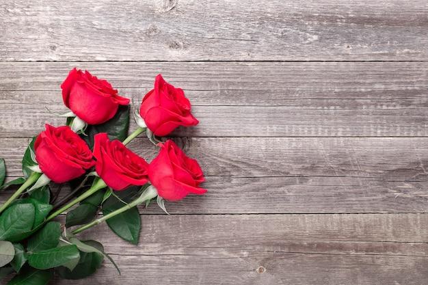 Fleurs roses rouges sur table en bois gris. carte de voeux de la saint-valentin. vue de dessus. copier l'espace - image