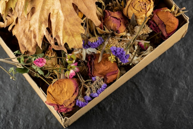 Fleurs de roses séchées avec des feuilles séchées dans une boîte en papier.