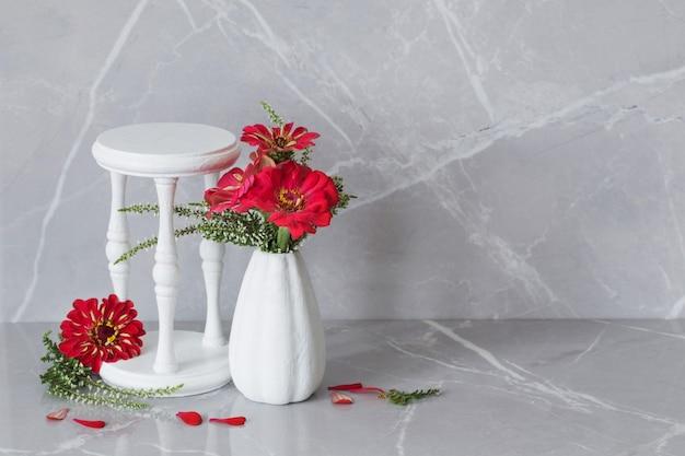 Fleurs rouges dans un vase blanc et un support en bois sur fond de marbre gris