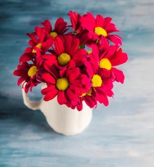 Fleurs rouges dans un vase sur une table grise