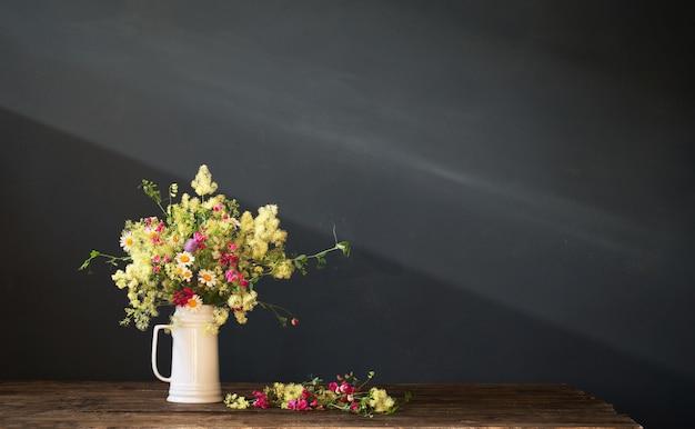 Fleurs sauvages dans une cruche blanche sur une surface sombre