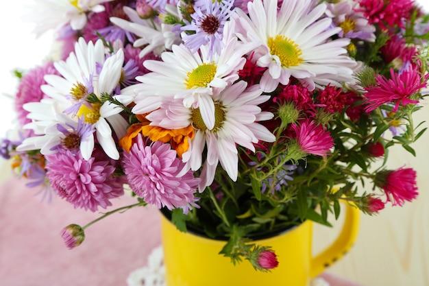 Fleurs sauvages dans la tasse sur la serviette sur la table en bois