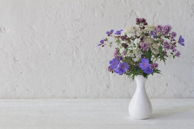 Fleurs sauvages dans un vase blanc sur fond blanc