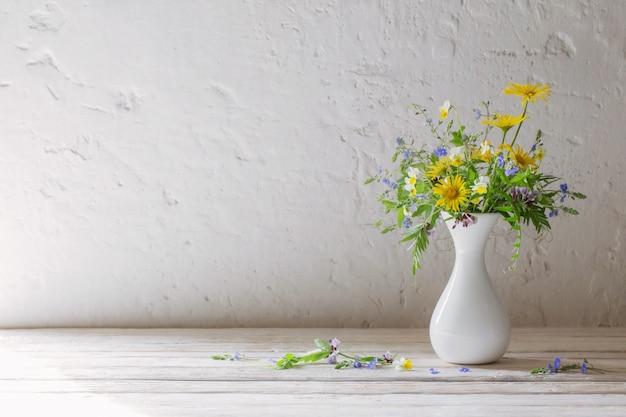 Fleurs sauvages dans un vase blanc sur fond vieux mur