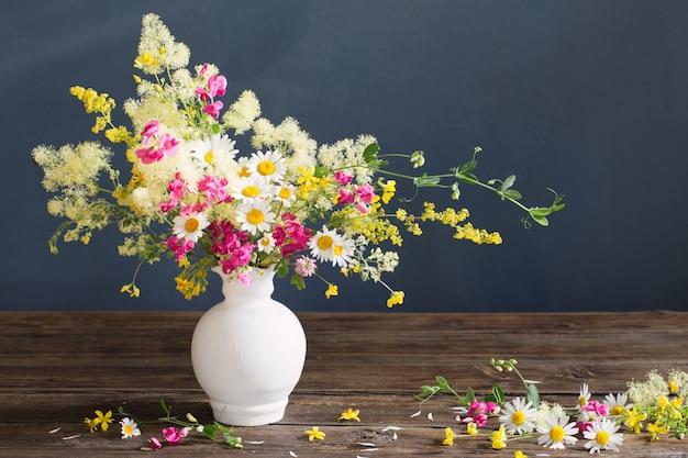 Fleurs sauvages dans un vase blanc sur un mur sombre