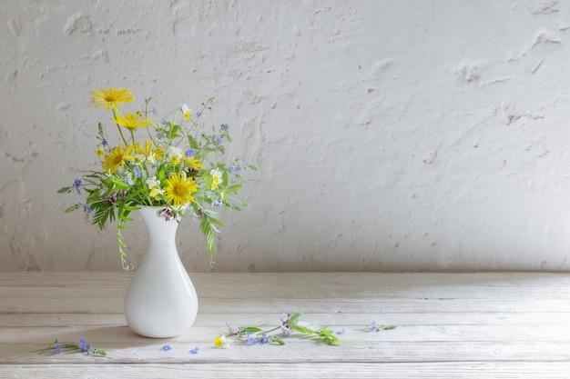 Fleurs sauvages dans un vase blanc sur vieux mur