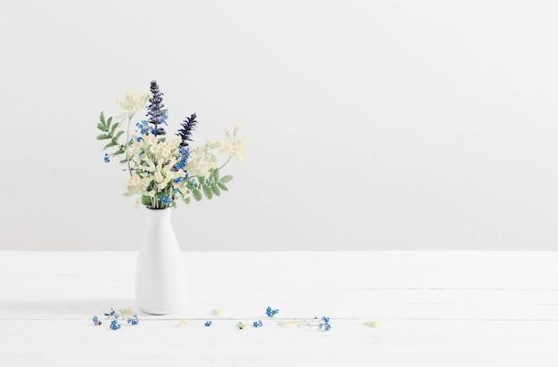 Fleurs sauvages dans un vase sur fond blanc