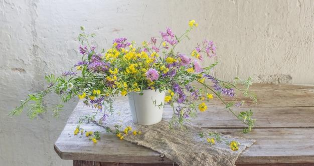 Fleurs sauvages d'été sur la vieille table en bois