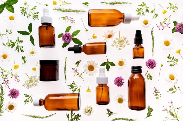 Fleurs sauvages et flacon en verre de médecine sur blanc