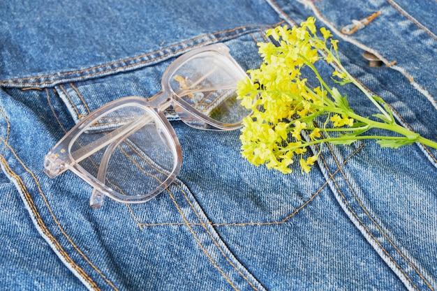 Fleurs sauvages jaunes et lunettes avec montures transparentes sur la poche de la veste en jean bleu, lunettes tendance