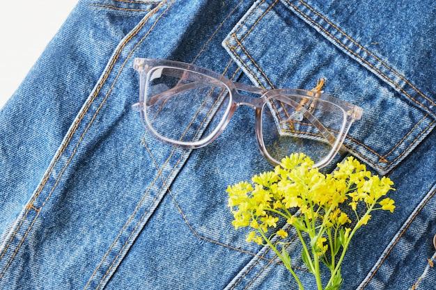 Fleurs sauvages jaunes et lunettes avec montures transparentes sur la poche de la vieille veste en jean bleu, lunettes tendance, style rétro