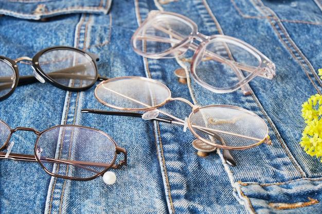 Fleurs sauvages jaunes et plusieurs lunettes sur une veste en jean bleue, lunettes tendance, vue de dessus de style rétro